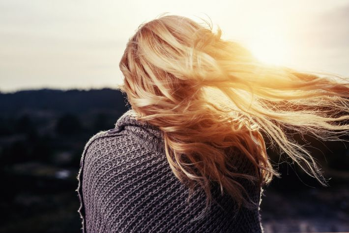 View of blonde haired woman from the back with hair blowing in the breeze